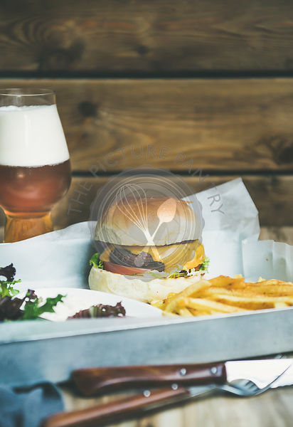 Classic burger dinner with french fries, salad and beer