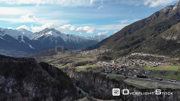 Aerial shot of river Inn with Alps and village in background in Tyrol, Austria