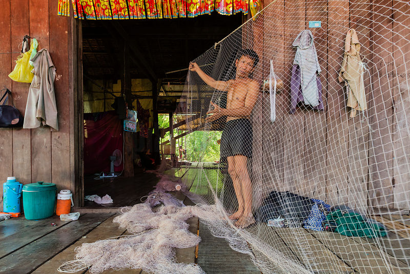 Fisherman Repairing Nets