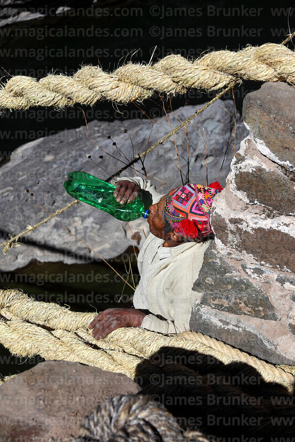 Man has a drink of chicha (maize beer) after tying rope to one of the main foundation ropes (so it can be tensioned), Q'eswac...