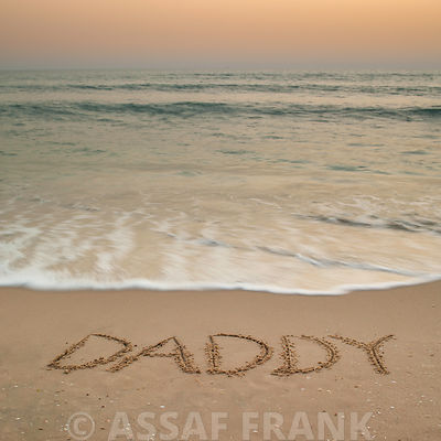 Sand writing - Word Daddy written on beach