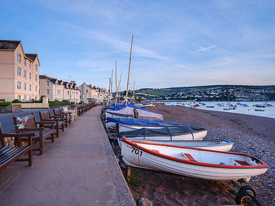 Boats and benches lined up along the top of the beach at Shaldon, Devon, UK