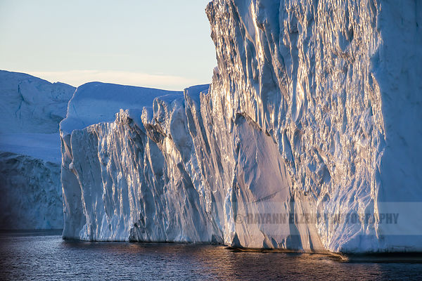 The side of an iceberg glitters in the golden morning sun in Ilulissat, Greenland