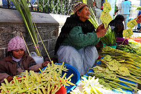 Girl and old lady selling crosses made out of palm leaves on Palm Sunday , La Paz , Bolivia