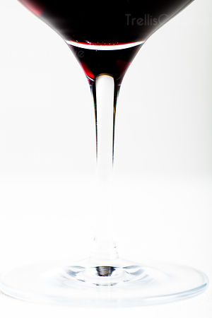 Close-up of red wine glass stem on a white background