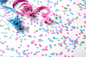 Carnival background with green, pink and blue confetti and serpentines on background