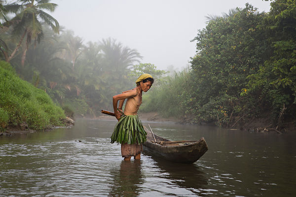 Mentawaï woman going to fish at dawn with her dugoutmade in a tree Meranti, the banana leaf loin is used to attract fish and ...