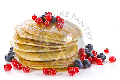 Small pancakes topped with honey, red currants and bilberries on white background