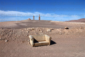 Abandoned old sofa and Presencias Tutelares statues, near Arica, Region XV , Chile