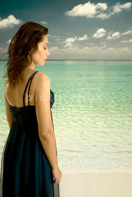 An atmospheric image of a woman in a blue dress walking on a tropical beach.