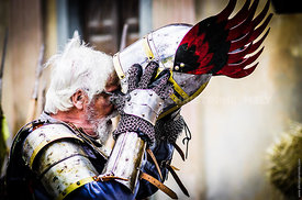 Glass wearing knight taking off his helmet in a medieval festival