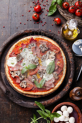 Italian pizza with meat, ham and mushrooms on wooden table