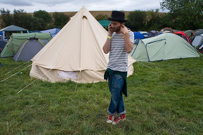 UK - Standon - A man makes a telephone call on his cellular mobile telephone next to a field of tents at the Standon Calling ...