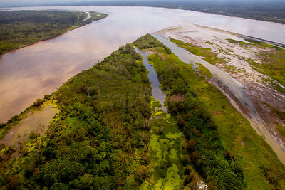 Aerial view of Amazon River, with settlements and secondary rainforest, near Iquitos, Peru. July 2015.