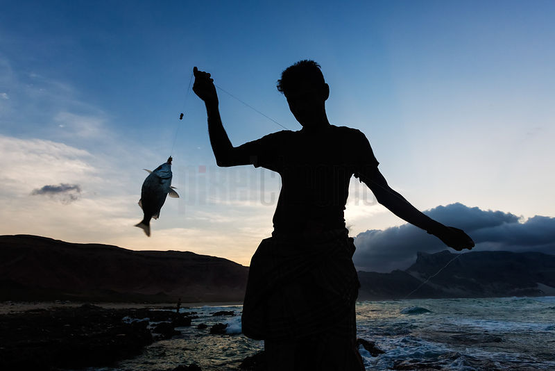 Silhouette of a Fisherman with Catch