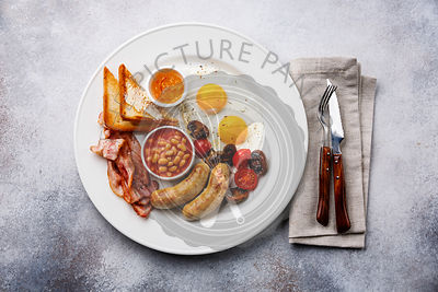 English breakfast with fried egg, sausage, bacon, beans and toast on white background
