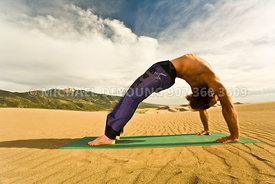Male yogi in back bend (urdhva Dhanurasana) pose - Great Sand Dunes National Park, CO