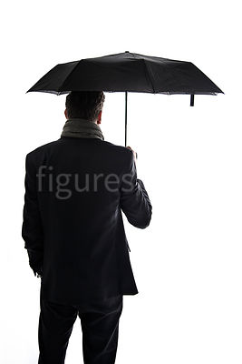 A mystery man in a suit, holding an umbrella, in semi-silhouette – shot from eye level.