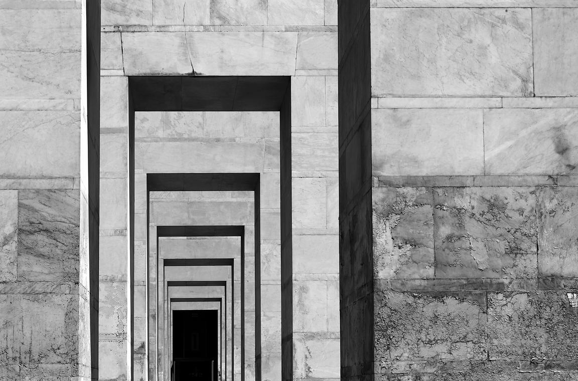 Tunnel_of_concrete_square_pillars_at_EUR_darkened_contrast