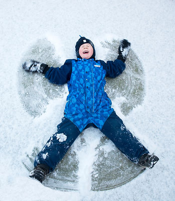 Child lying in the snow creating snow angel, Norway, January 2014. Model released.