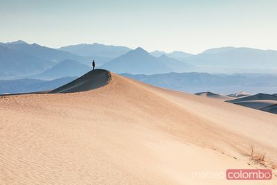 Man standing on a sand dune at sunrise, Death valley , USA