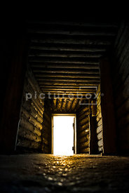 An atmospheric, low perspective image of a darkly lit underground tunnel / bunker.