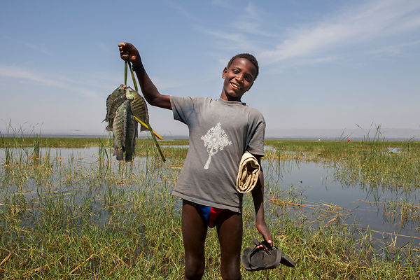 Aboulé, 13 ans, montre le résultat de sa pêche sur son tankwa, Awasa, Éthiopie / Aboulé, 13, shows the result of his fishing ...
