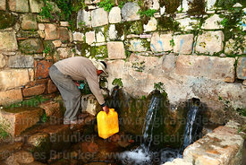 Local man getting water from the fountain of the Inca near Yumani, Sun Island, Lake Titicaca, Bolivia