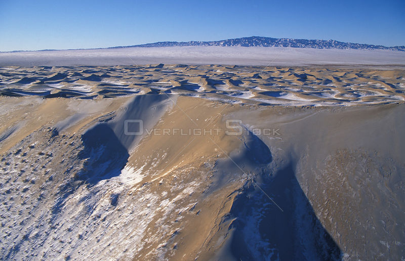 Aerial view of sand dunes with snow, Gobi Desert, Mongolia, January 2004. Filmed for BBC Planet Earth series.