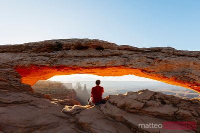 Uomo che si gode l'alba all'arco di Mesa, Canyonlands, USA