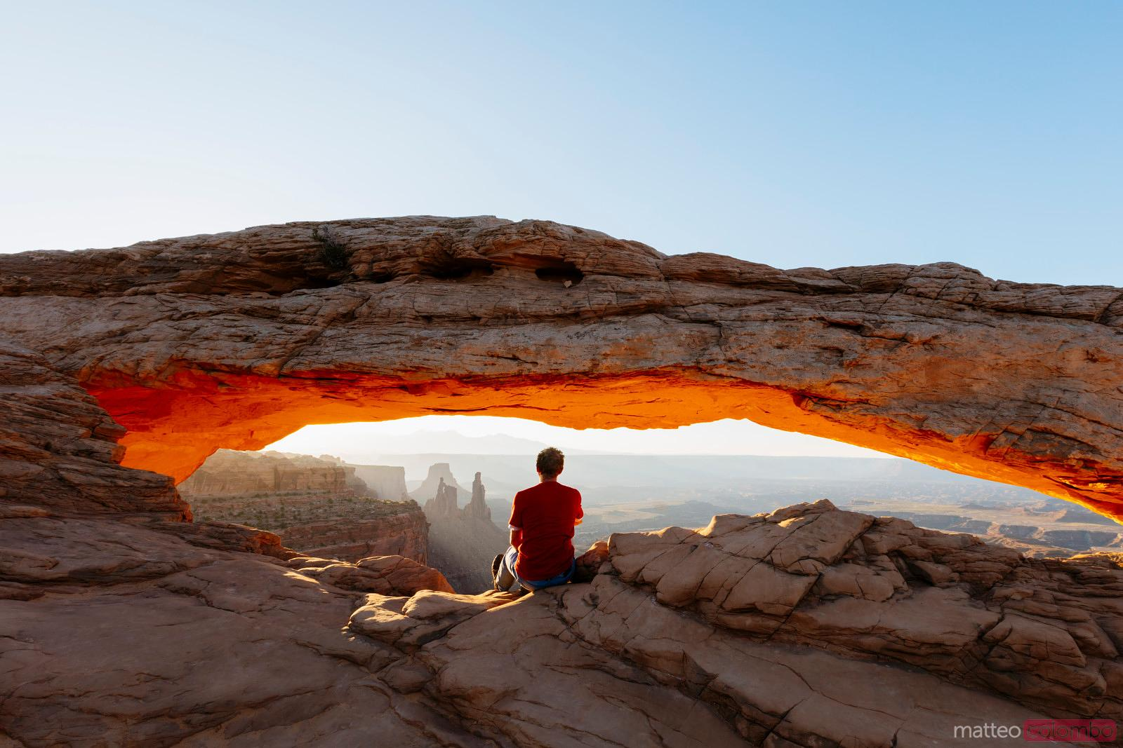 Man enjoying sunrise at Mesa arch, Canyonlands, USA