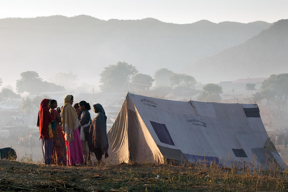 Women gather outside a tent at sunrise in Pushkar, Rajasthan, India