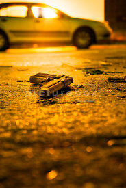 An atmospheric image of discarded gun in a car park, with a mystery man sitting in a car behind.