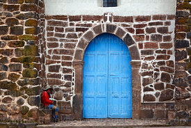 Girl sitting next to entrance of colonial church, Raqchi, Cusco Region, Peru