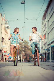 Young couple riding bicycles together, Osijek, Croatia