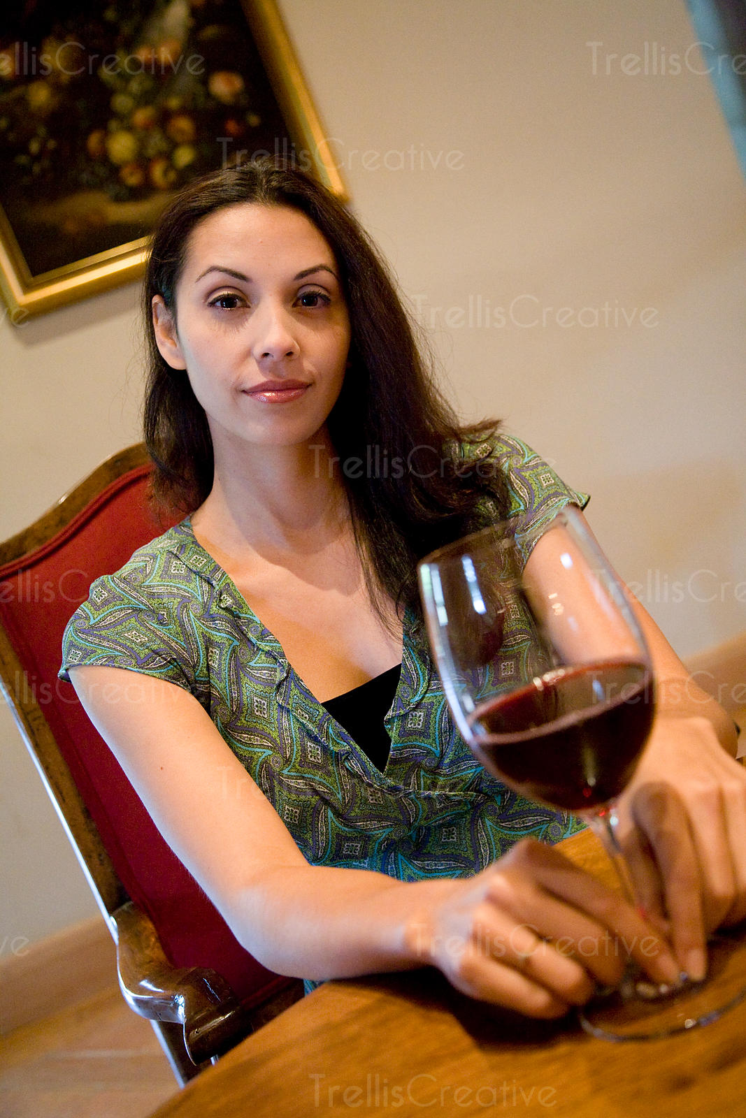young woman sits at table with glass of red wine