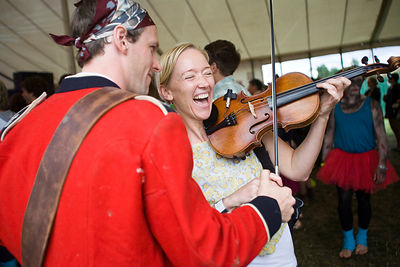 UK - Standon - A woman laughs as she plays a violin at the Standon Calling Festival
