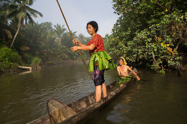 Women going to go fishing on their dugout made in a tree Meranti (Shorea sp.), banana leaf loin cloth is used to attract fish...