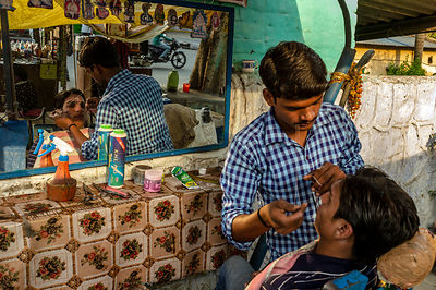 A Barber Threads A Man's Eyebrows At A Roadside Stall