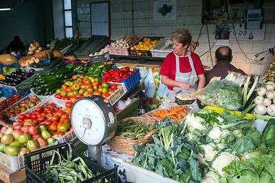 A woman setting up her vegetable stall in the Mercado do Bolhão, Porto, Portugal