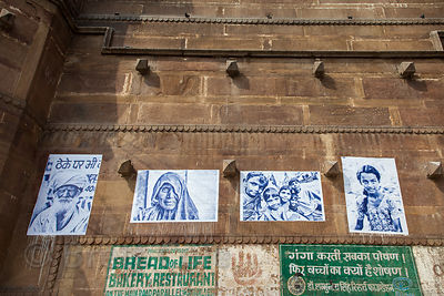 Prints of photos of local people hang on a wall on the ghats in Varanasi, India.