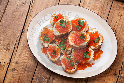 Sandwiches with Salmon red caviar and parsley on white plate on wooden background