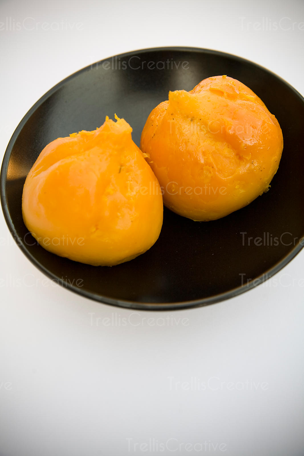 Two golden yellow roasted and peeled beets in a dark bowl