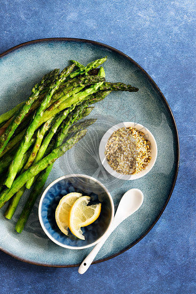 Chargrilled asparagus spears with bowls of lemon slices and pistachio dukkah.