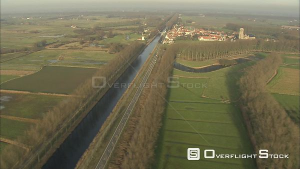 Flying above a canal past Oostkerke and PAND Hotel in Damme, Belgium