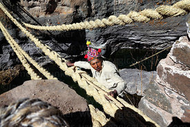 Man ties rope to one of the main foundation ropes once it is in position so it can be tensioned, Q'eswachaka , Canas province...