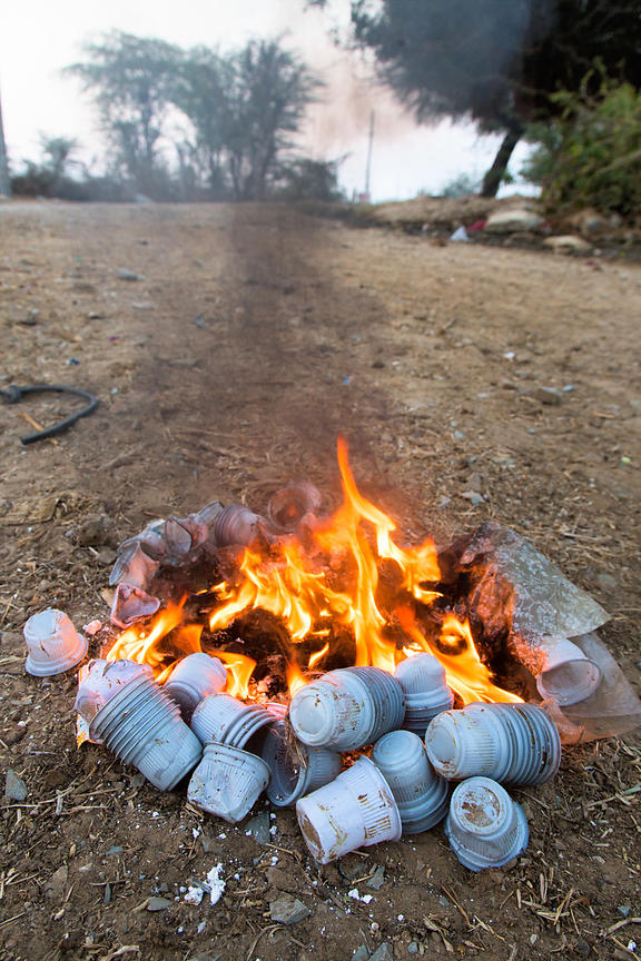 Plastic chai tea cups burn in a fire to keep people warm on a cold winter morning in the desert, Majhewla village, Rajasthan,...