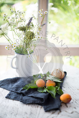 Apricots and onions with grey kitchen towel and flower bouquet on white wooden table with garden view in the background
