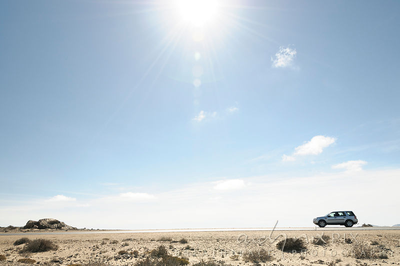 A 4x4 (sport utility vehicle) on a flat road in a desert, sunbeams shining down from above, clear blue sky