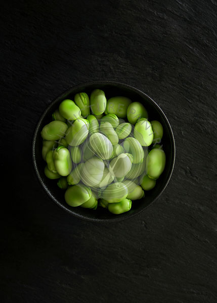 Raw fava beans in a bowl.